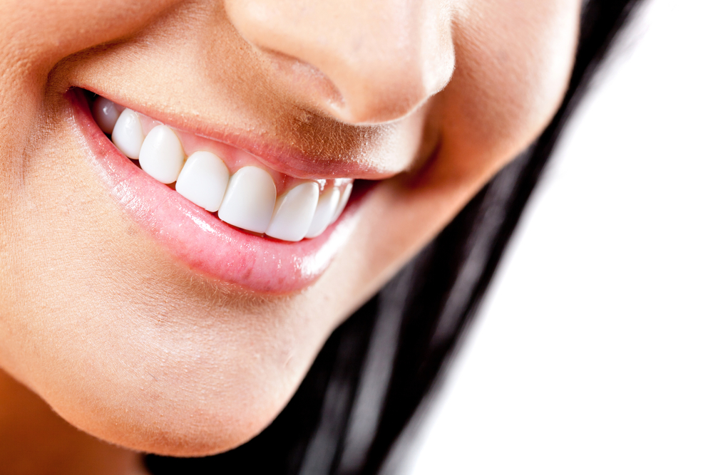 Close-up to beautiful female smile - isolated over a white background